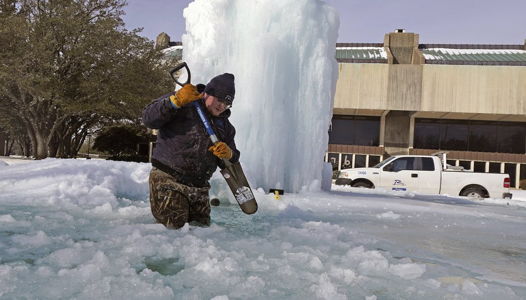 City of Richardson, TX worker Kaleb Love breaks ice on a frozen fountain. (AP Images)