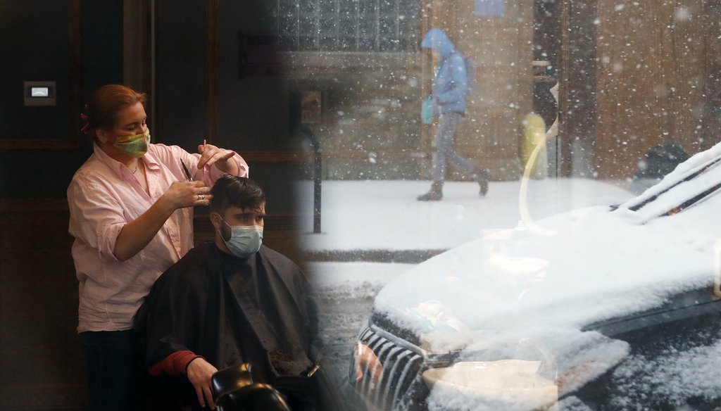 Gina Loukas, left gives a haircut to Ryan as a lone pedestrian is reflected in the barbershop window Monday, March 15, 2021, as fresh snow falls in Chicago. (AP Images)