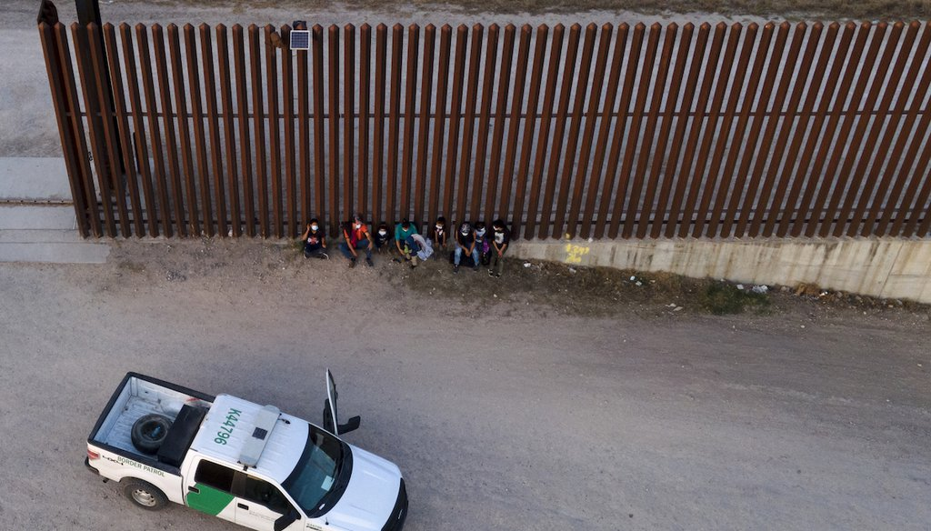 A U.S. Customs and Border Protection vehicle is seen next to migrants after they were detained and taken into custody, Sunday, March 21, 2021, in Abram-Perezville, Texas. (AP/Cortez)