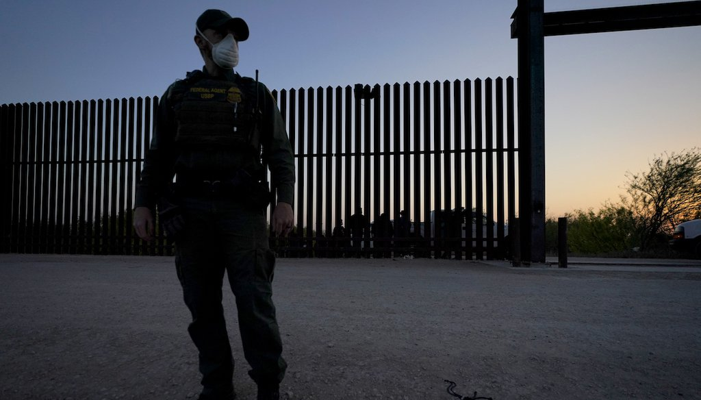 A U.S. Customs and Border Protection agent looks on near a gate on the U.S.-Mexico border wall as agents take migrants into custody, Sunday, March 21, 2021, in Abram-Perezville, Texas. (AP/Cortez)