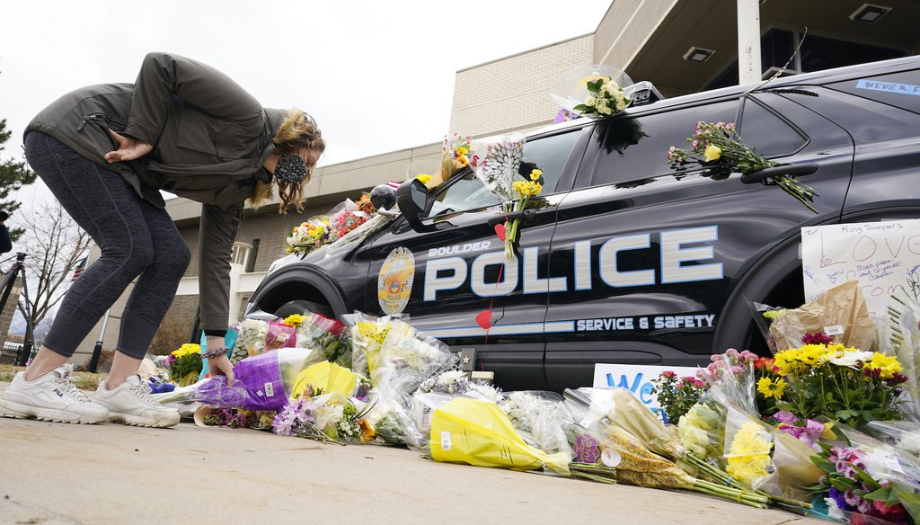 A woman leaves a bouquet of flowers next to a police cruiser parked outside the Boulder Police Department after an officer was one of the victims of a mass shooting at a King Soopers grocery store Tuesday, March 23, 2021, in Boulder, Colo.  (AP Images)