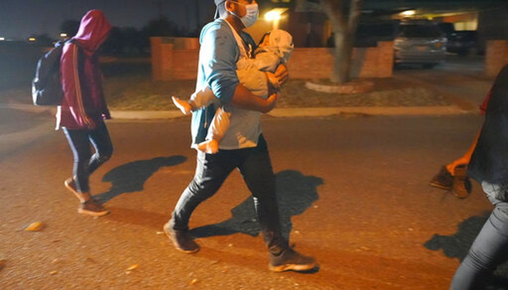 A migrant carries a child to an intake area after turning themselves in upon crossing the U.S.-Mexico border on March 24, 2021, in Roma, Texas. (AP)