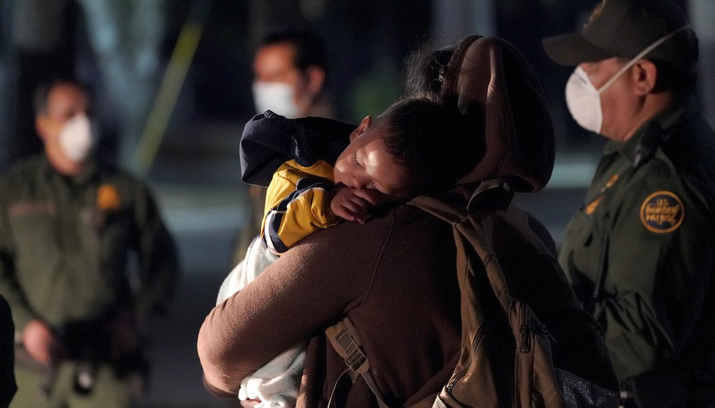 A migrant child sleeps on the shoulder of a woman at an intake area after turning themselves in upon crossing the U.S.-Mexico border, March 24, 2021, in Roma, Texas. (AP)