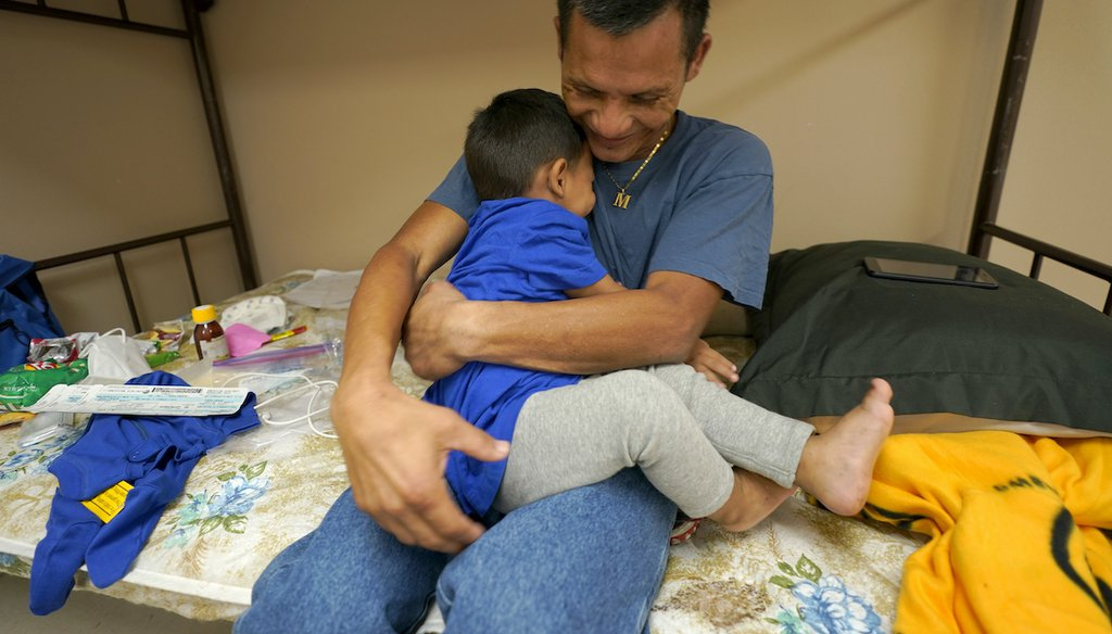 Elmer Maldonado, top, a migrant from Honduras, hugs his 1-year-old son at a shelter, March 22, 2021, in Harlingen, Texas. They spent a week in immigration custody after crossing the Rio Grande through Texas to request asylum. (AP)