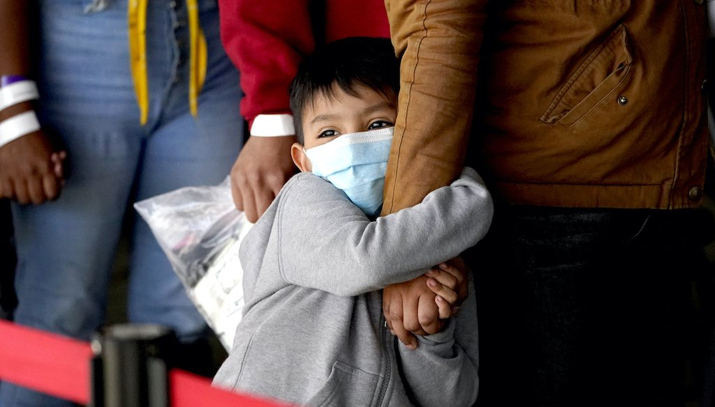 A migrant child holds onto a woman's arm as they wait to be processed by a humanitarian group after being released from U.S. Customs and Border Protection custody at a bus station, March 17, 2021, in Brownsville, Texas. (AP)