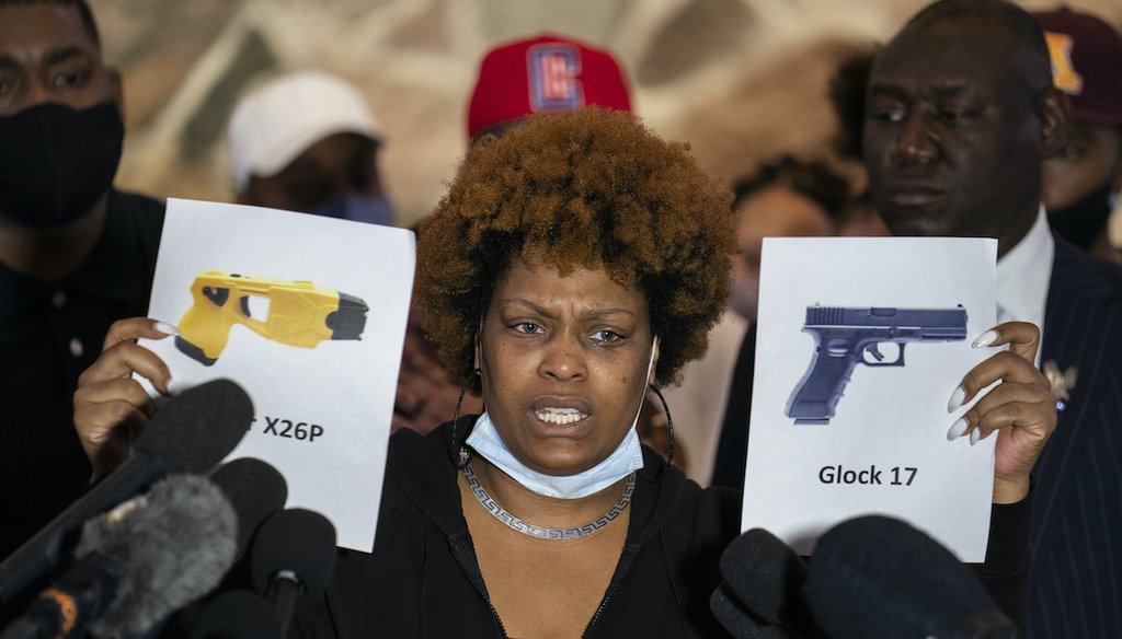 Naisha Wright, aunt of the deceased Daunte Wright, holds up images depicting X26P Taser and a Glock 17 handgun during a news conference at New Salem Missionary Baptist Church, April 15, 2021, in Minneapolis. (AP)