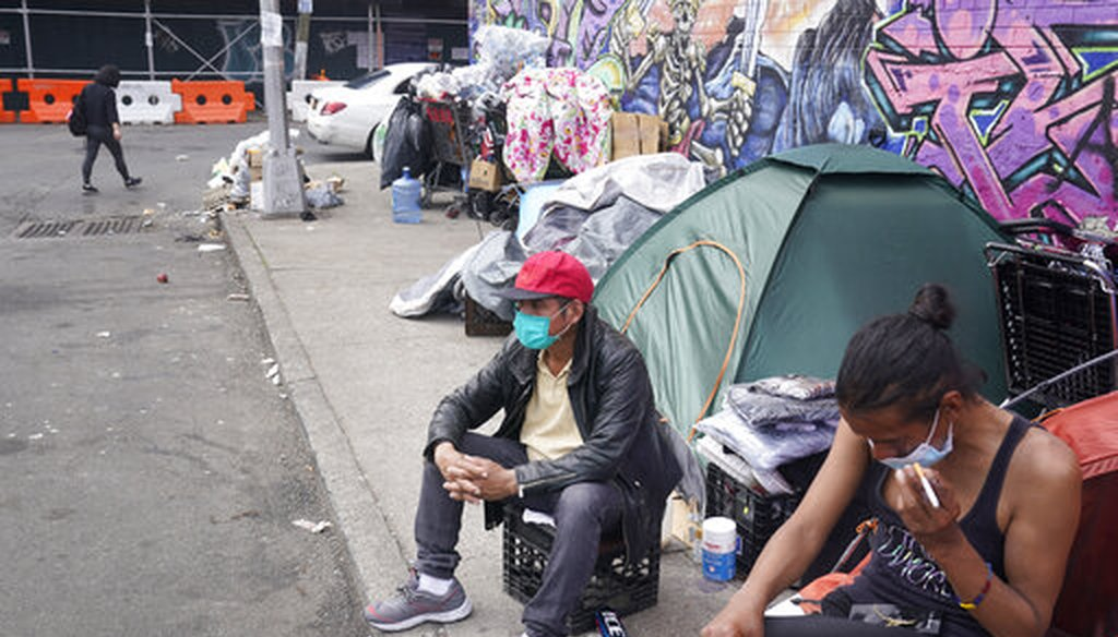 Sotero Cirilo, center, sits on the sidewalk at a homeless encampment where he sleeps in Queens, New York, on April 14, 2021. (AP)