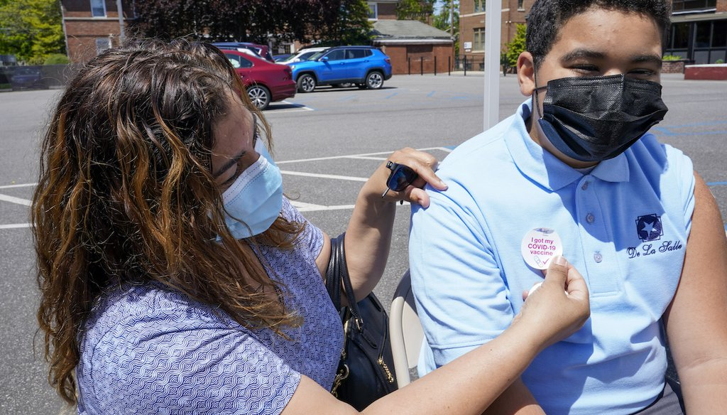 Kendy Marte, left, places a sticker on her son Stanley Pena, 13, after he received the first dose of the Pfizer COVID-19 vaccine at the De La Salle School, on May 14, 2021, in Freeport, N.Y. (AP)