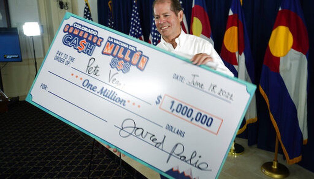 Peter Vegas of Boulder, Colo., takes a super-sized check after he was named the third of five weekly $1 million winners for being vaccinated against COVID-19 on June 18, 2021. (AP)