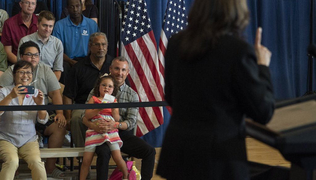 Stella Quatrini, center, is held as she watches Vice President Kamala Harris speak about the child tax credit during an event at Brookline Memorial Recreation Center in Pittsburgh, June 21, 2021. (AP)