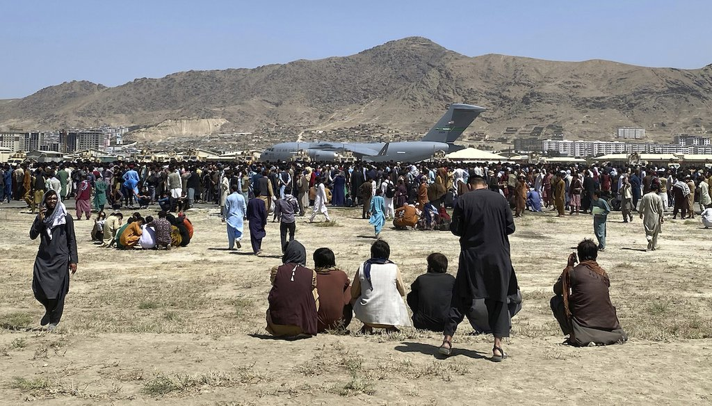 Hundreds of people gather near a U.S. Air Force C-17 transport plane at the perimeter of the international airport in Kabul, Afghanistan on Aug. 16, 2021. (AP/Rahmani)