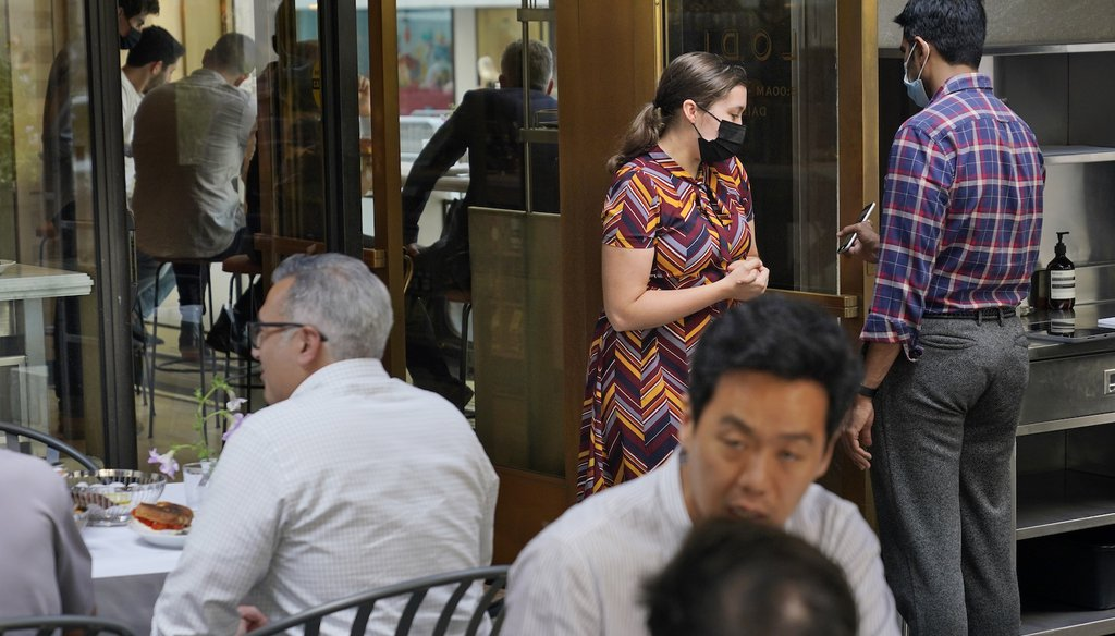 A maitre d' checks guests' proof of vaccination at a restaurant in midtown Manhattan in New York, Monday, Sept. 13, 2021. (AP)