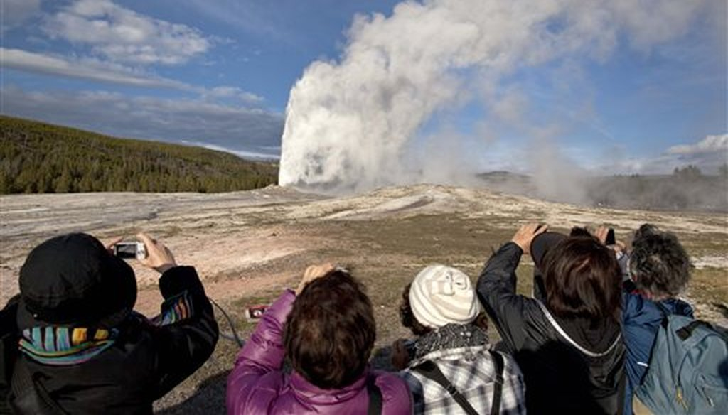 In this May 21, 2011 file photo, tourists photograph Old Faithful erupting, at Yellowstone National Park, in Mont. Old Faithful is among the park's hydrothermal features powered by the Yellowstone supervolcano. (AP Photo/Julie Jacobson,File)