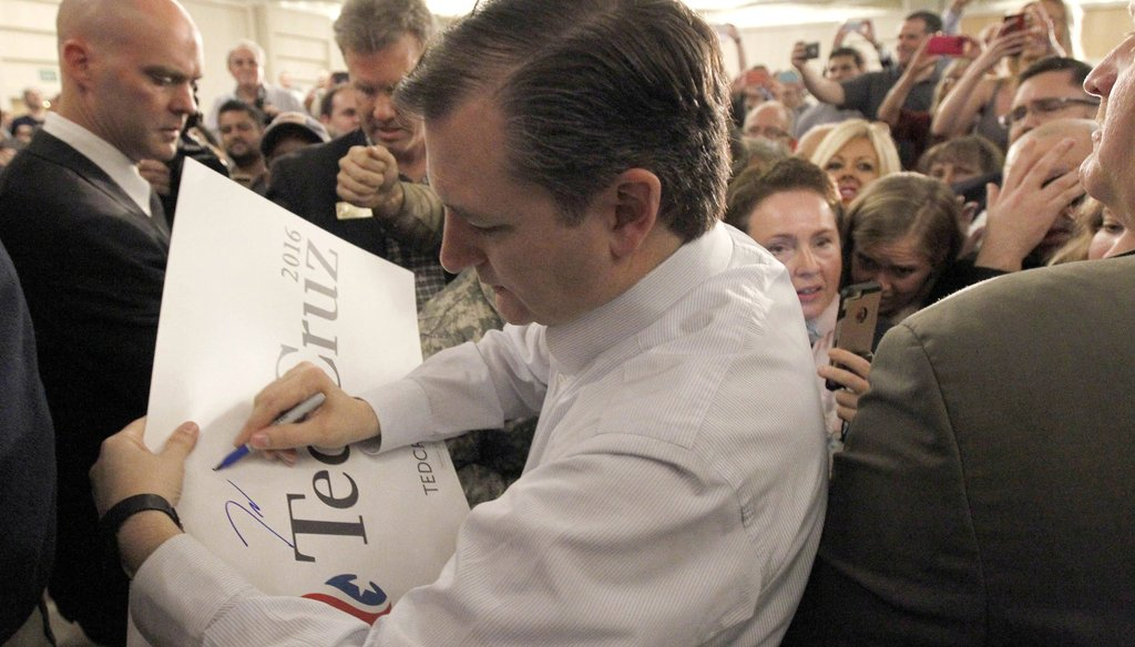Republican presidential candidate Sen. Ted Cruz, R-Texas, signs an election poster after a rally in Irvine, Calif. on Monday, April 11, 2016. (AP Photo/Nick Ut)