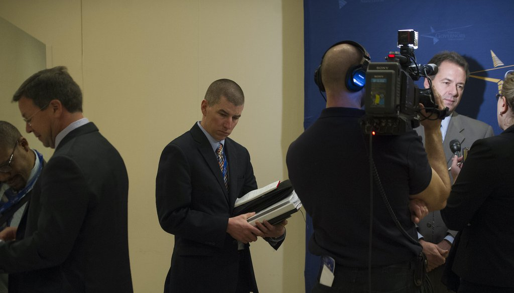 Kevin O'Brien, former deputy chief of staff, center, to Montana Gov. Steve Bullock, at right, holds briefing books as Bullock is interviewed by a television crew in 2014. (AP)