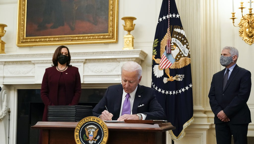 President Joe Biden signs executive orders alongside Vice President Kamala Harris and Dr. Anthony Fauci, director of the National Institute of Allergy and Infectious Diseases, in the White House on Jan. 21, 2021, in Washington. (AP/Brandon)