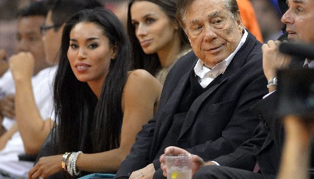 Los Angeles Clippers owner Donald Sterling, right, and V. Stiviano, left, watch the Clippers play the Sacramento Kings during the first half of an NBA basketball game in Los Angeles. (AP)
