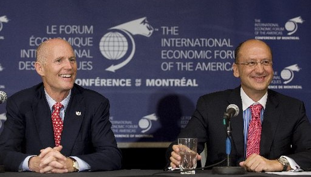 Florida Gov. Rick Scott, left, and president and CEO of Garda World Stephan Cretier, laugh during a news conference at the International Economic Forum of the Americas in Montreal, June 8, 2011.