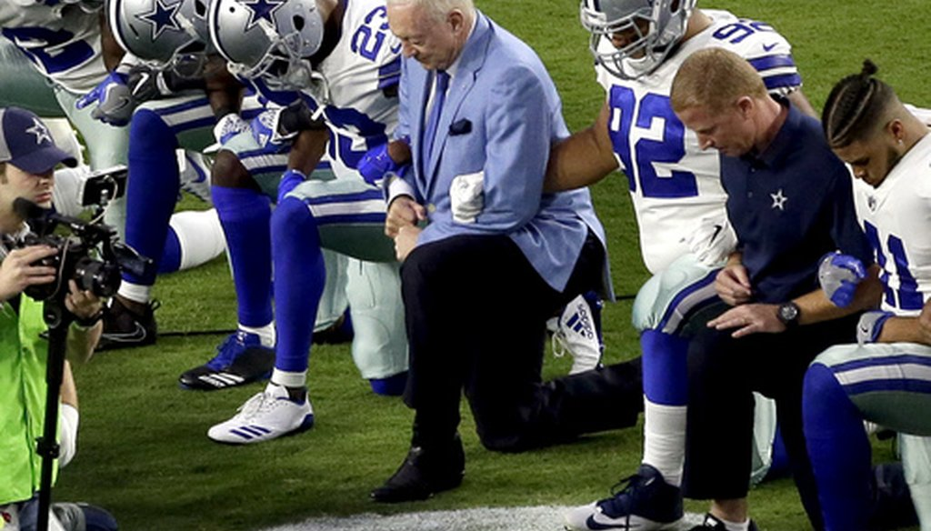 The Dallas Cowboys, led by owner Jerry Jones, center, take a knee prior to the national anthem before an NFL football game against the Arizona Cardinals in Glendale, Ariz.,  Sept. 25, 2017. (Associated Press).