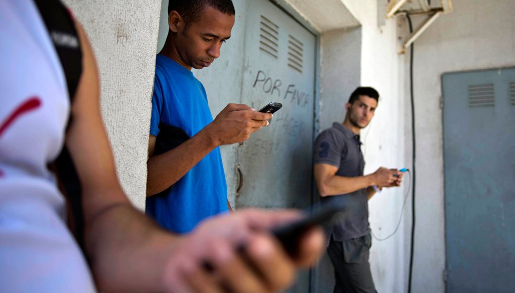 Students stand outside a building to find an Internet signal for their phones in Havana, Cuba, on April 1. (AP Photo)