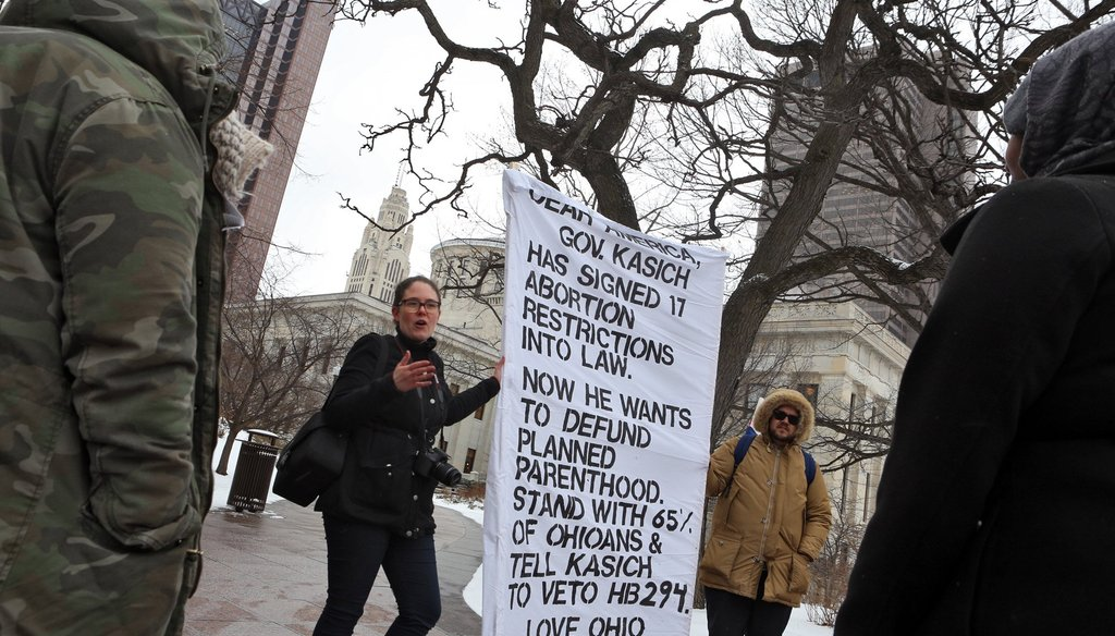 Anne Morrice of Planned Parenthood, Chris Maxie of Planned Parenthood, talk to Zahra Farah and Asha Abdulle of Columbus about the bill presented to Gov. John Kasich to defund Planned Parenthood at the Ohio Statehouse Feb. 10. (Columbus Dispatch via AP)
