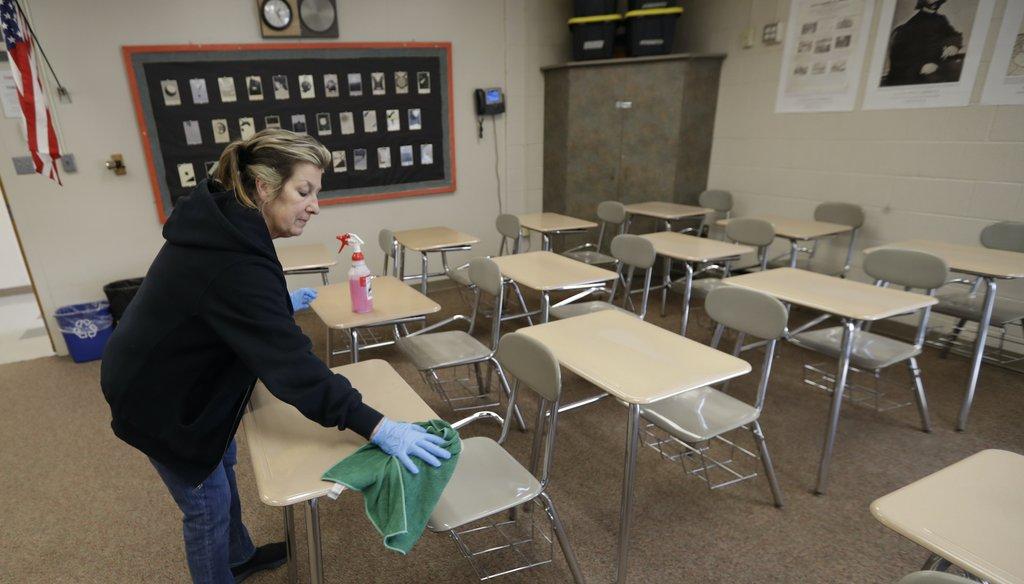 Custodian Patti Alesci cleans desks at Orange High School, Monday, March 16, 2020, in Pepper Pike, Ohio. (AP)