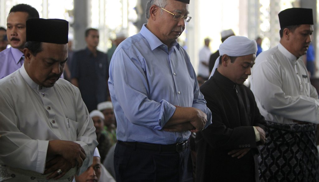 The missing Malaysian airliner is a mystery with evolving leads every day. Here, Malaysian Prime Minister Najib Razak (second from left, prays at a mosque in Sepang, Malaysia, on March 14, 2014. (AP photo)