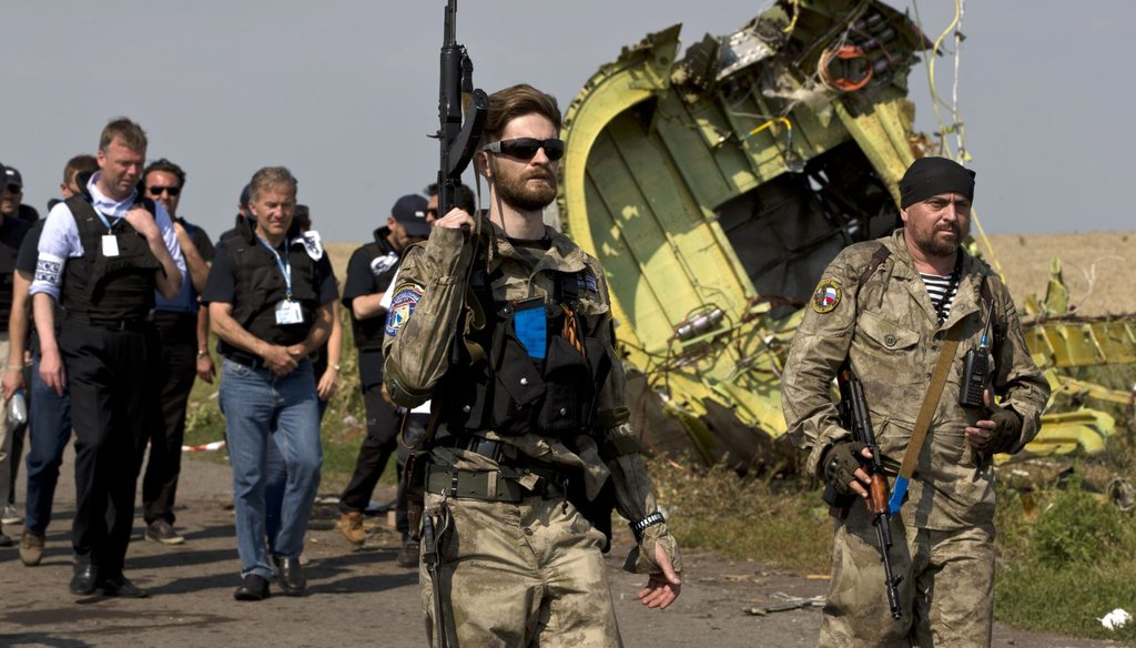 Pro-Russian rebels, right, walk by plane wreckage as they arrive for a media briefing at the crash site of Malaysia Airlines Flight 17 on July 22, 2014. (AP Photo)
