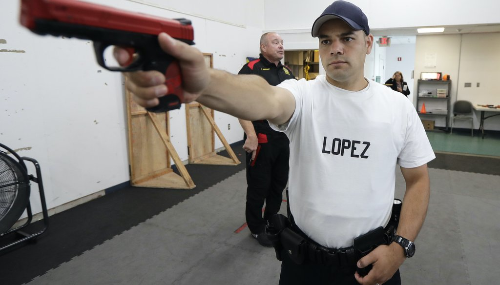 In this July 16, 2019, photo, Fernando Lopez, of the Othello Police Department in Othello, Wash., holds a training gun as he takes part in a firearms defense class as part of Washington state's Basic Law Enforcement Academy in Burien, Wash. (AP)