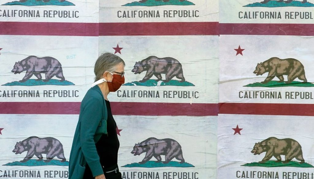A pedestrian wearing a mask walks in front of a billboard displaying California flags in San Francisco, April 30, 2020, during the coronavirus outbreak. AP Photo/Jeff Chiu