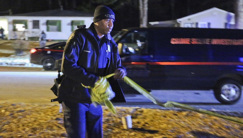 An Atlanta police officer gathers crime scene tape after the shooting investigation of a man found dead inside a vehicle in a city driveway in February. Photo by John Spink / AJC