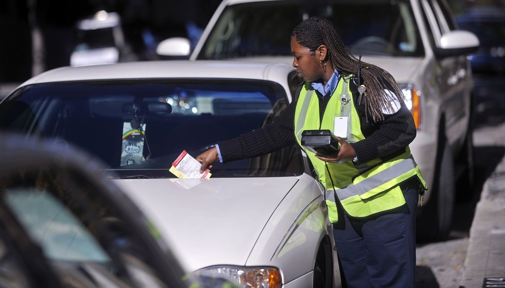 A PARK-atlanta agent leaves a ticket on the windshield of a car with an expired metered space in 2010 in downtown Atlanta. AJC file photo
