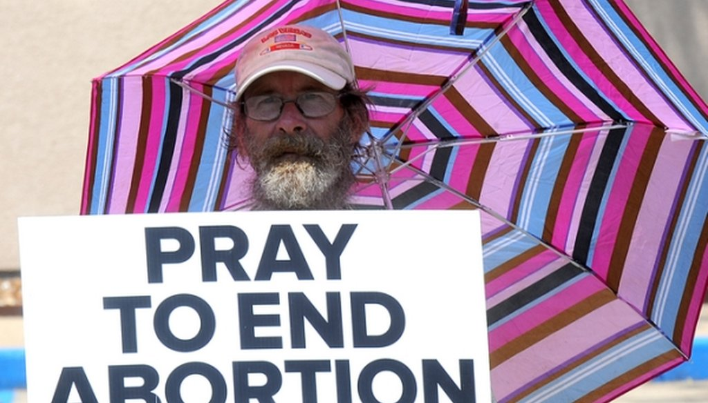 A protester holds a sign in front of Planned Parenthood of Kansas and Mid-Missouri in Columbia, Mo., on July 28, 2015. (Don Shrubshell/Columbia Daily Tribune via AP)