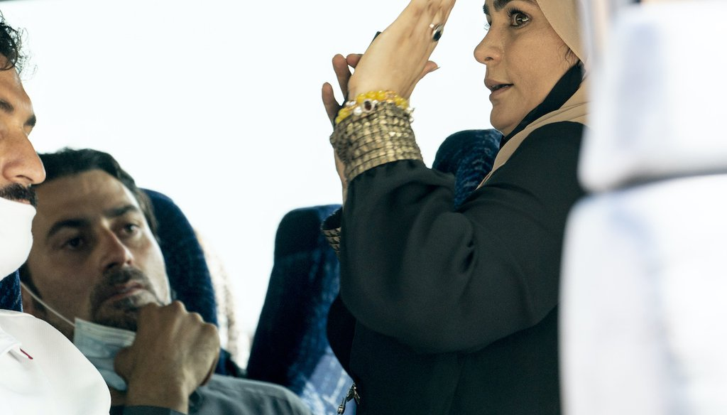 A woman steps onto an arriving bus carrying Afghanistan refugees to give them instructions as they arrive at a processing center in Chantilly, Va., Monday, Aug. 23, 2021, after arriving on a flight at Dulles International Airport. (AP)