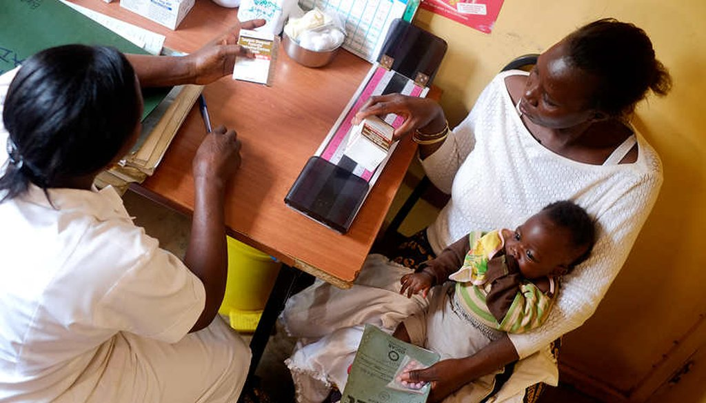 A health care worker provides drugs to a mother living with HIV in Uganda. (UNAIDS)
