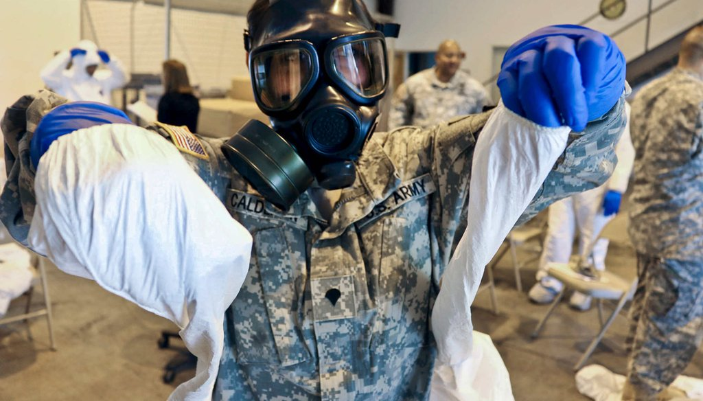 Army Spc. Kristal Calderon practices donning and removing protective equipment and a mask after a class at the logistical warehouse on Fort Gordon, Ga., Oct. 14, 2014.(U.S. Army)