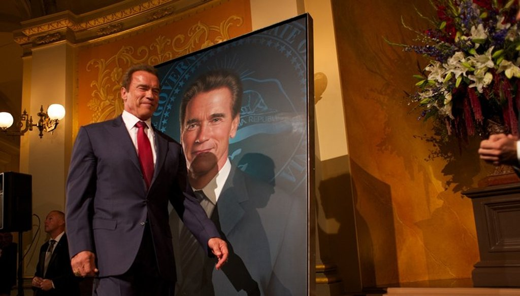 Former California Gov. Arnold Schwarzenegger walks past his portrait unveiled at the state Capitol in 2014. Andrew Nixon / Capital Public Radio