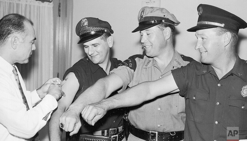 The first four of more than 500 police, firemen and deputy sheriffs in St. Joseph County to receive Asian flu vaccine bare their arms for Dr. William J. Stogdill in South Bend, Ind., on Aug. 30, 1957. (AP)