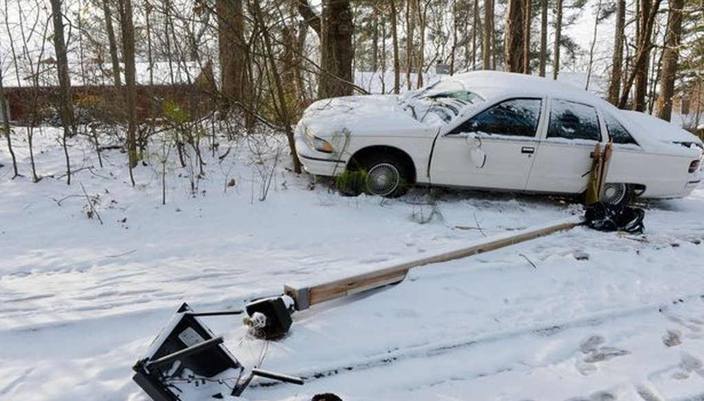 A vehicle sits along a road in Stone Mountain, Ga. after hitting a light pole. Metro Atlanta is suffering through the grips of snow and ice from Tuesday's rough weather. Photo credit: Kent Johnson/AJC.
