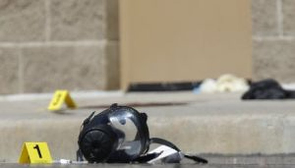 Yellow markers sit next to evidence, including a gas mask, as police investigate the scene outside the Century 16 movie theater east of the Aurora Mall in Aurora, Colo., the site of one of the deadliest mass shootings in recent U.S. history.