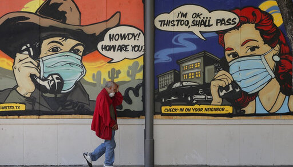A man wearing face protection walks past a mural painted on a border up business closed due to the COVID-19 pandemic, Monday, April 27, 2020, in Austin, Texas. (AP)