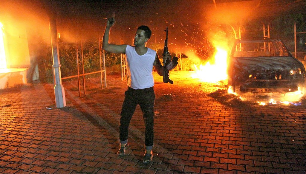 An armed man waves his rifle as buildings and cars are engulfed in flames after being set on fire inside the U.S. compound in Benghazi, Libya, late on Sept. 11, 2012.