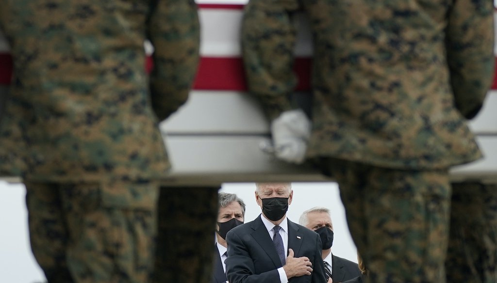 President Joe Biden holds his hand to his heart as a carry team transfers the remains of Marine Corps Lance Cpl. Kareem M. Nikoui, 20, at Dover Air Force Base. Nikoui was one of 13 U.S. service members who were killed in Afghanistan. (AP Photo)