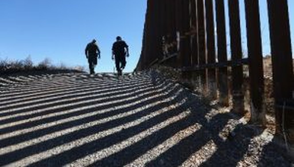 U.S. Customs and Border Protection personnel walk along a section of recently-constructed fence on the U.S.-Mexico border near Nogales, Ariz.