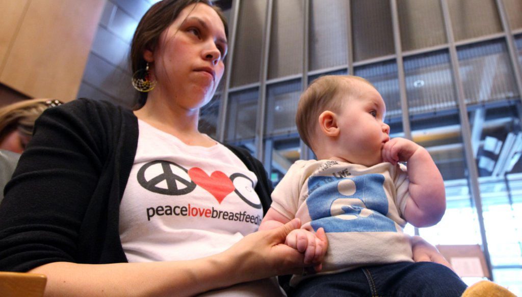 A woman holds her daughter after testifying in front of the Seattle City Council, April 9, 2012 (AP).