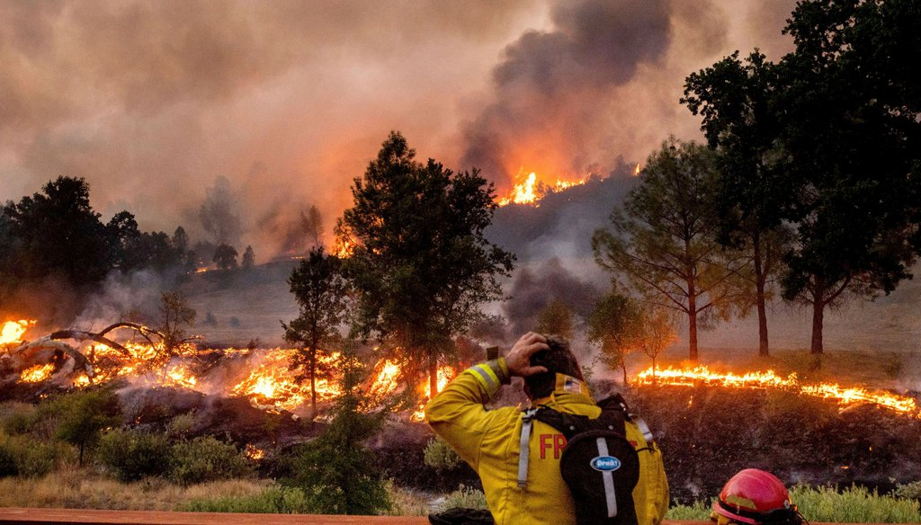A firefighter rubs his head while watching the LNU Lightning Complex fires spread through the Berryessa Estates neighborhood of unincorporated Napa County, Calif., on Friday, Aug. 21, 2020. Noah Berger / AP Photo