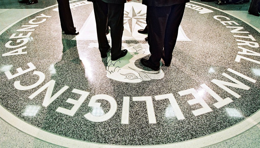 President George W. Bush and CIA Director George Tenet stand on the agency's seal at CIA headquarters in Langley, Va., March 20, 2001. The Senate released a report on a CIA interrogation program under Bush last week.