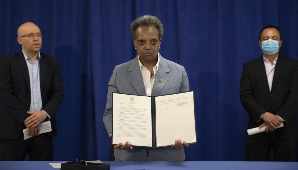 Mayor Lori Lightfoot signs an executive order on April 7, 2020 to ensure coronavirus-related benefits offered by the city of Chicago are available to immigrants and refugees. (Ashlee Rezin Garcia/Sun-Times)