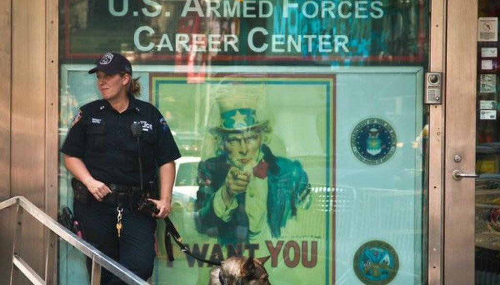 An NYPD anti-terrorism officer stands guard with a K-9 unit at a military recruiting station in Times Square, on July 17, 2015. Security at military recruiting centers will be reviewed in the aftermath of a shooting in Tennessee. (AP/Bebeto Matthews)