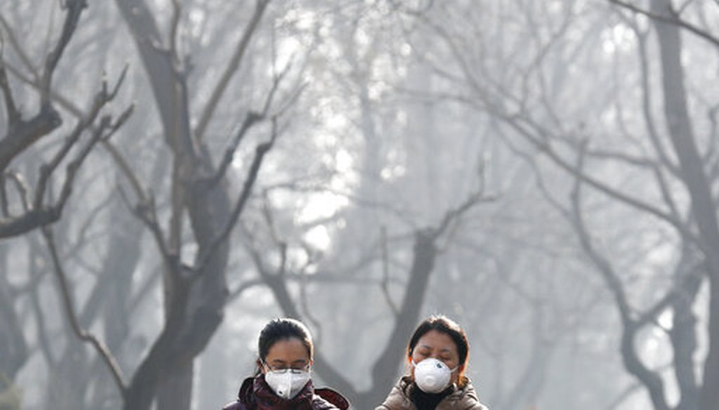 In this Dec. 19, 2016, file photo, women wearing masks to protect themselves from air pollution walk through Ritan Park shrouded by dense smog in Beijing. (AP)